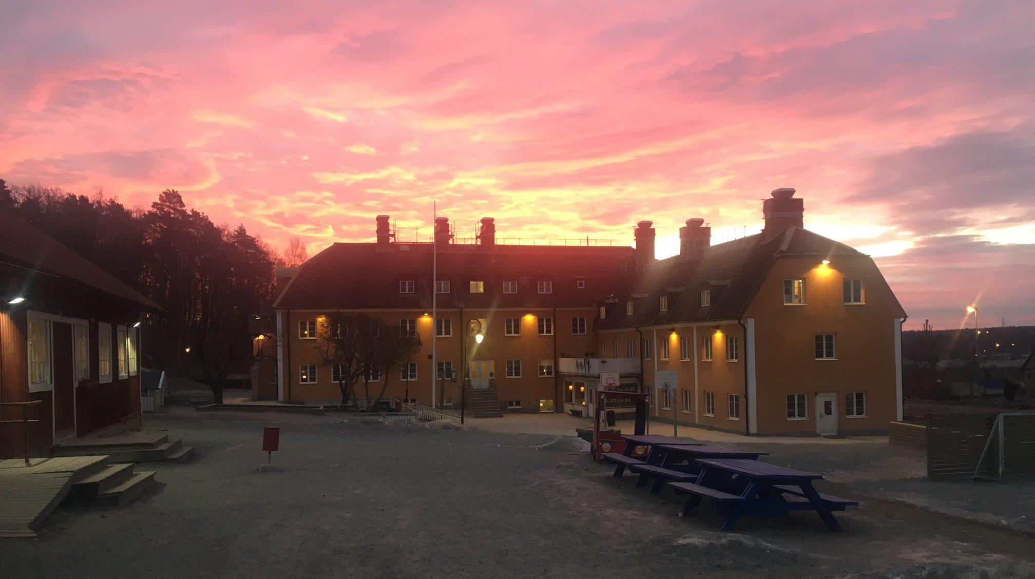 Skolbyggnad med vacker rosa kvällshimmel